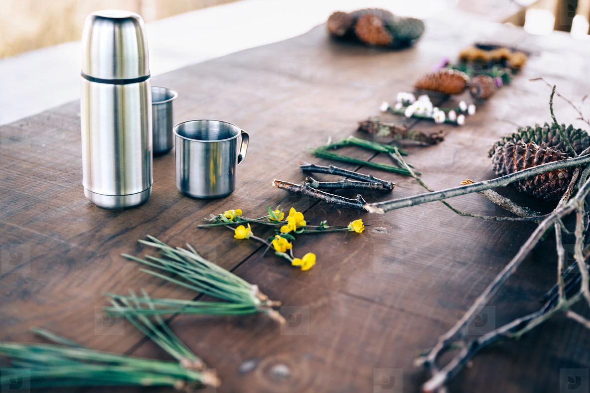 Table with thermos  cups and forest objects