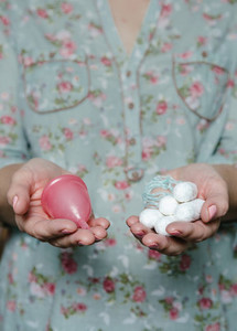 Woman holding in hands tampons and menstrual cup