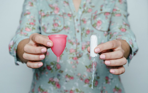 Woman hands comparing menstrual cup with a tampon