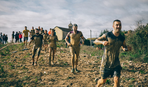 Participants in a extreme obstacle race running