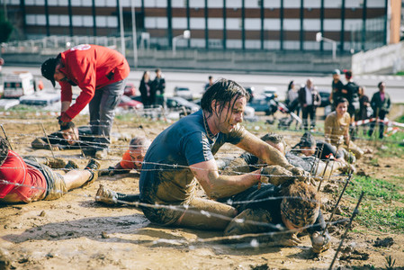 Runner helping to woman crawling under barbed wire in a test of extreme obstacle race