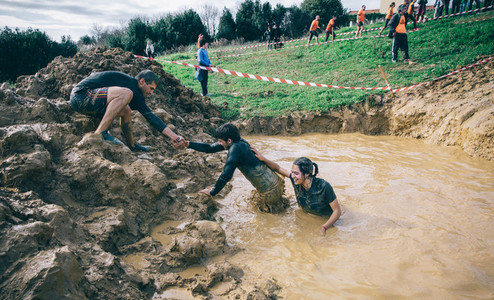 Team helping to cross mud pit in a test of extreme obstacle race