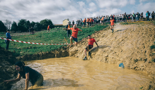 Runner jumping to mud pit in a test of extreme obstacle race