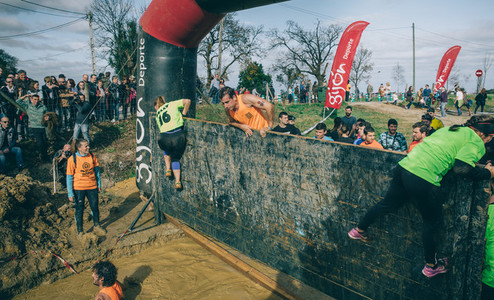 Runners climbing wall in a test of extreme obstacle race