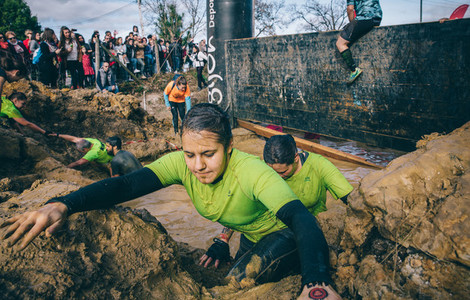 Runner crossing mud pit in a test of extreme obstacle race