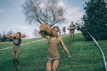 Runners carrying wooden logs in a test of extreme obstacle race