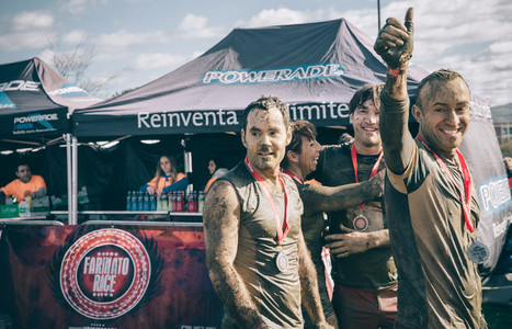 Runners with medals celebrating their victory in a extreme obstacle race