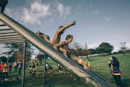 Runners going down structure in a test of extreme obstacle race