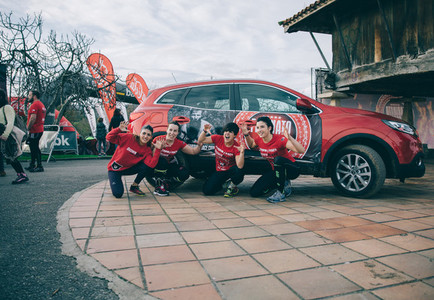Runners team posing in front of car before the race