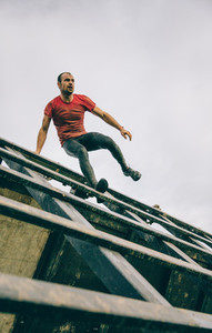 Runner going down wall in a test of extreme obstacle race