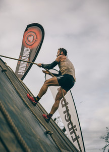 Runner climbing wall with a rope in a test of extreme obstacle race