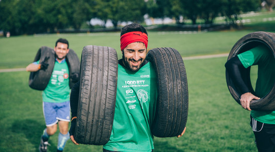 Runner carrying tires in a test of extreme obstacle race