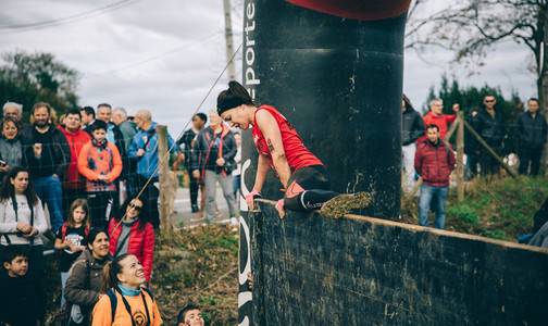 Runner climbing wall in a test of extreme obstacle race