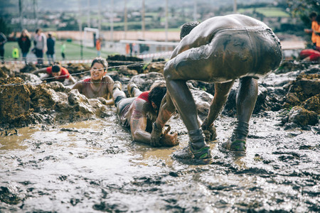 Runner helping woman to crawling under barbed wire in a test of extreme obstacle race