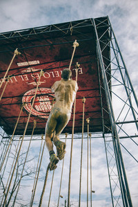 Dirty runner climbing rope in a test of obstacle race