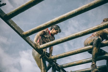 Runner climbing structure in a test of extreme obstacle race