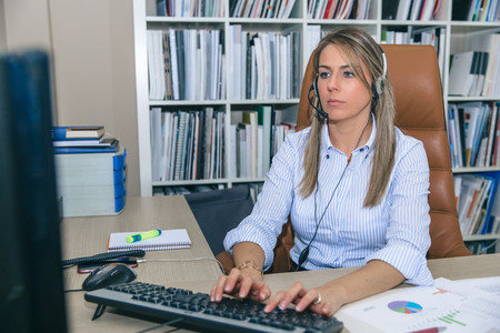 Blonde secretary working with computer in office