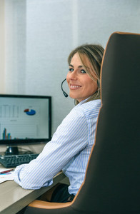 Smiling blonde secretary working with computer in office