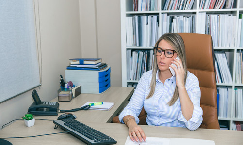 Blonde businesswoman talking with phone in the office