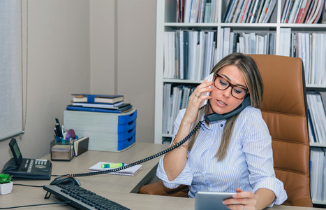 Busy businesswoman talking with cell and fixed line phone in office