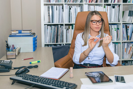 Bored blonde secretary polishing nails in the office