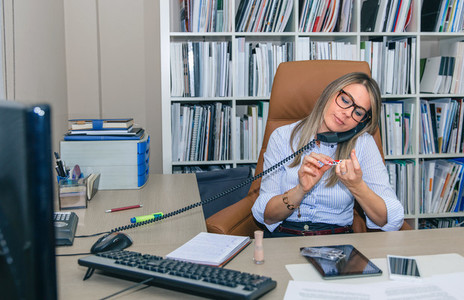 Bored secretary polishing nails and talking on phone