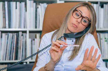 Bored secretary polishing nails and talking on phone