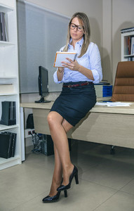 Young woman with crossed legs writing notes