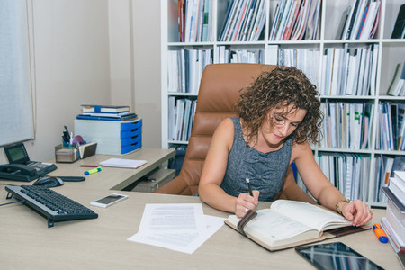 Businesswoman writing in notebook sitting in the office