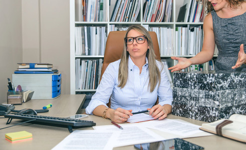 Tired secretary with lot of work in the office