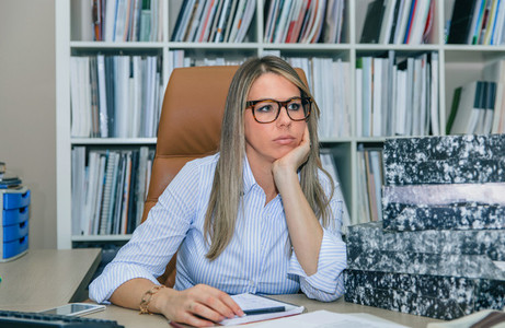 Bored secretary with lot of work in office
