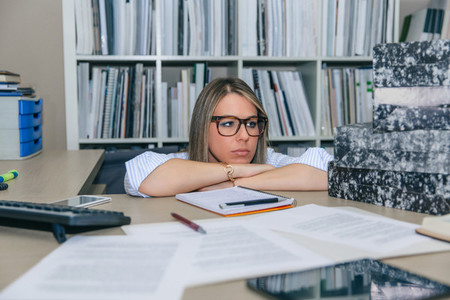 Exhausted secretary with folders stack in the desktop