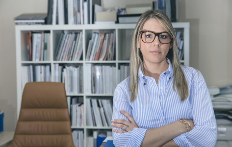 Young businesswoman with glasses standing in office