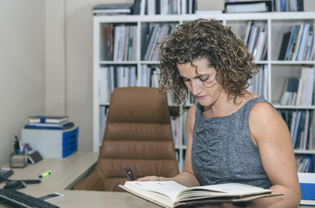 Businesswoman review notebook in office against of bookcase