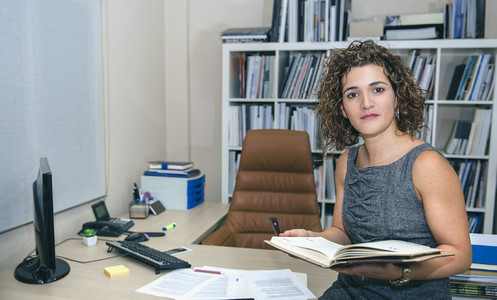 Businesswoman holding notebook sitting over desktop table
