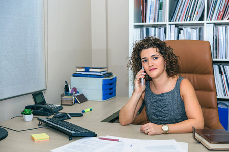 Smiling businesswoman talking with phone in the office