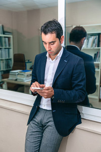 Businessman looking his smartphone in the office