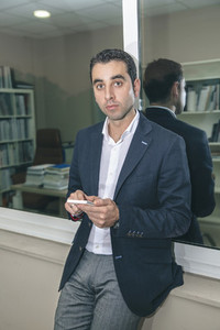 Businessman looking at camera while holding smartphone