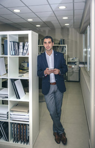 Businessman smiling and holding smartphone in office