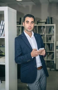 Businessman holding smartphone leaning on a bookcase