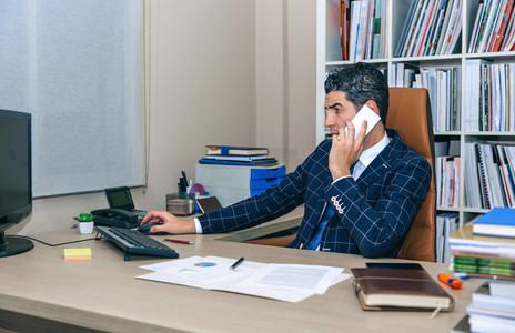 Businessman talking on smartphone and working with computer