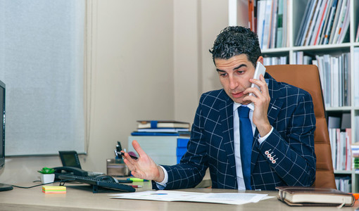 Businessman having discussion by phone in office
