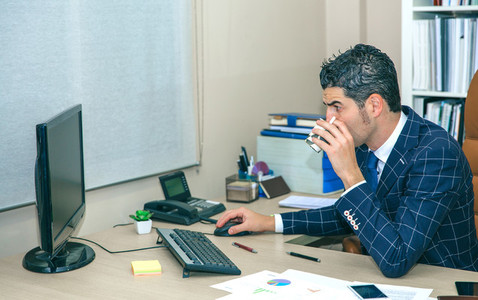 Businessman drinking coffee and working with computer