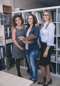 Three businesswomen standing working in the office