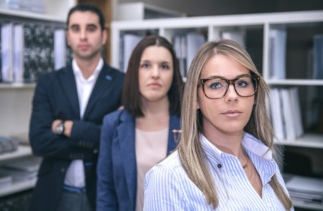 Businesswoman looking at camera with colleagues in background