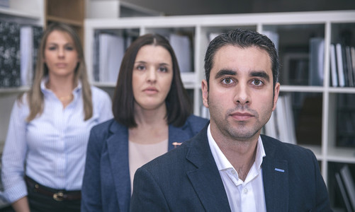 Businessman looking at camera with colleagues in background