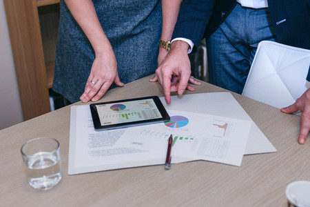 Unrecognizable colleagues with tablet and documents in meeting