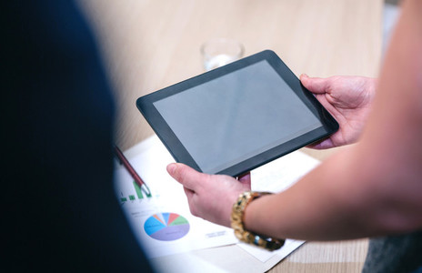 unrecognizable woman holding tablet in business meeting