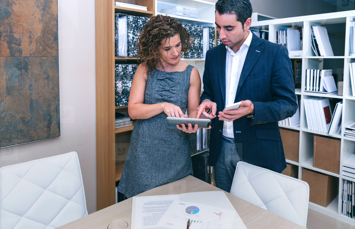 Business colleagues looking documents in electronic devices