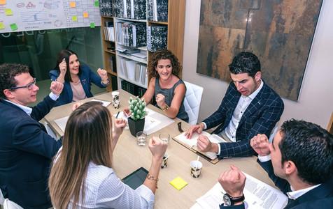 Teamwork celebrating business success in company headquarters